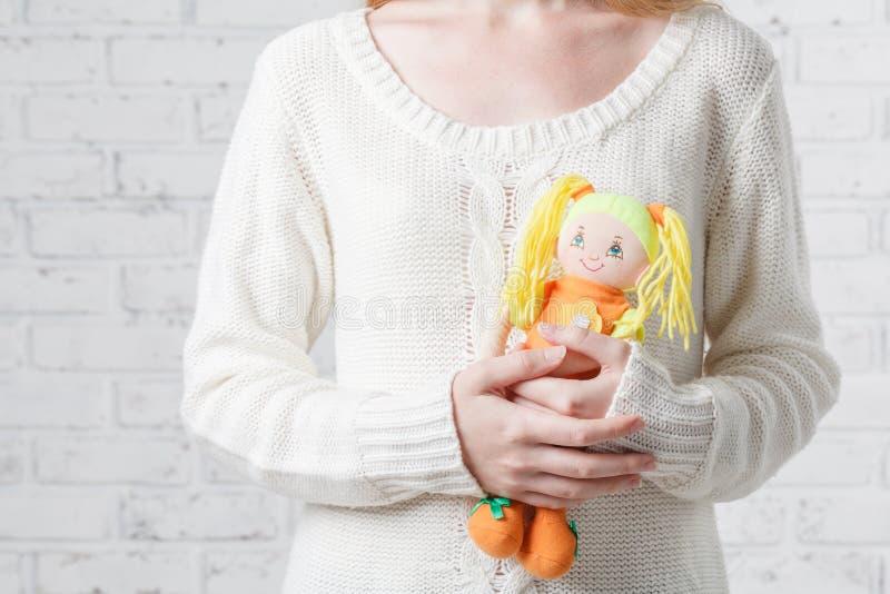 Belle jeune femme tenant la poupée dans le salon près du windo images libres de droits