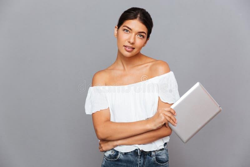 Belle jeune femme tenant la tablette et regardant l'appareil-photo image libre de droits