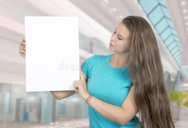 Belle jeune femme tenant une bannière blanche image libre de droits