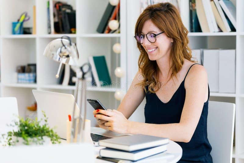 Belle jeune femme travaillant avec son téléphone portable à la maison images stock