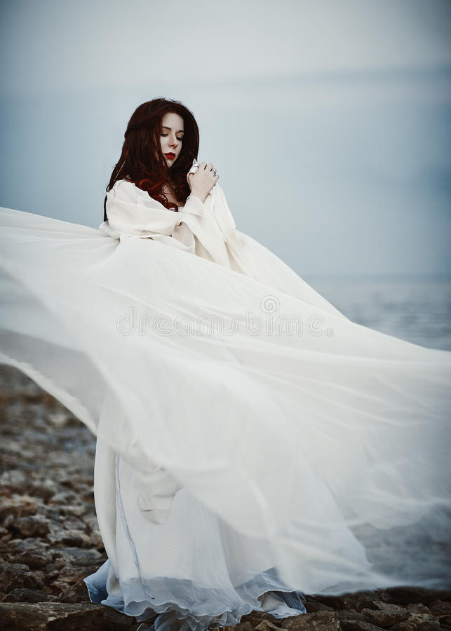 Belle jeune femme triste dans la robe blanche se tenant sur la plage de mer image libre de droits