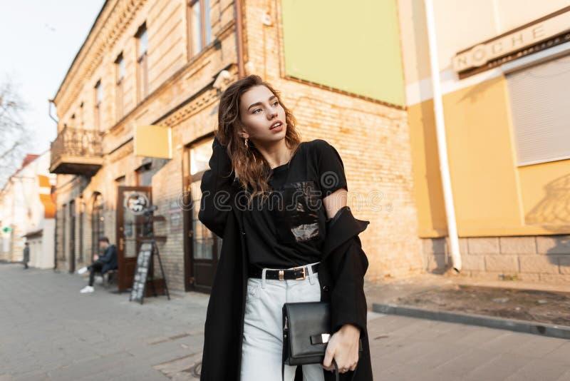 Belle jeune femme urbaine de brune dans un long manteau élégant dans un T-shirt à la mode dans des jeans blancs avec un sac en cu photos stock