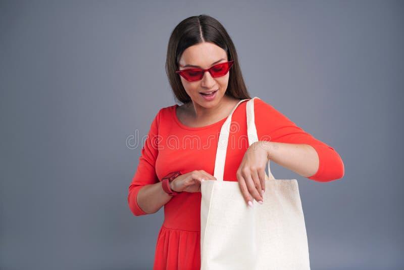 Belle jeune femme vérifiant le contenu du sac d'emballage image libre de droits
