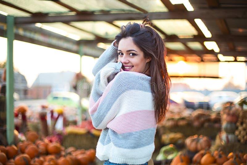 Belle jeune fille à la mode au fond de correction de potiron d'automne Avoir l'amusement et pose images libres de droits