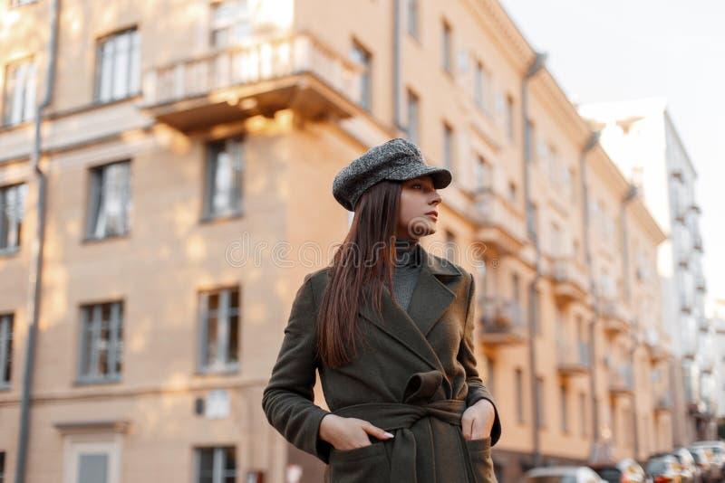 Belle jeune fille élégante élégante dans un chapeau de cru et un manteau vert de mode marchant sur une rue européenne près du bât image stock
