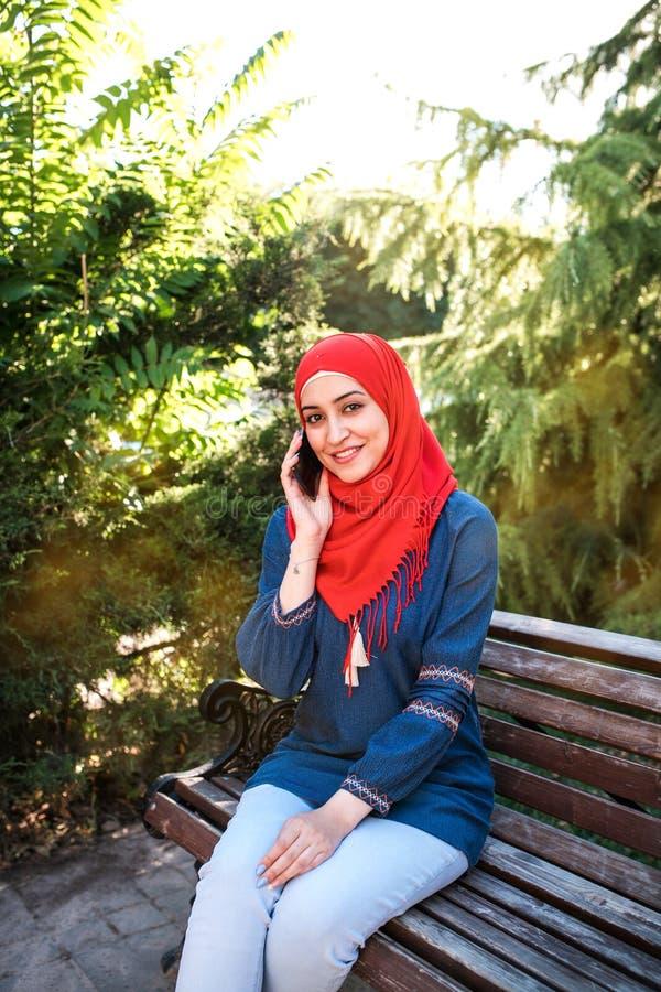 Belle jeune fille arabe dans le hijab posant pour une caméra à la rue d'été photos libres de droits
