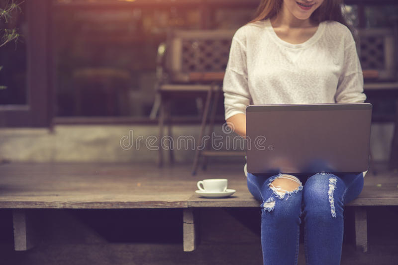 Belle jeune fille asiatique travaillant à un café avec un lapto photo stock