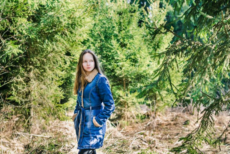 Belle jeune fille avec de longs cheveux blonds dans une veste bleue de denim dans une for?t verte une journ?e de printemps ensole photos stock