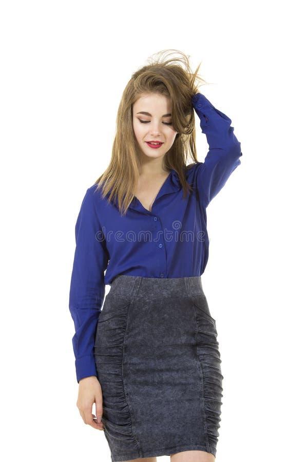 Belle, jeune fille avec de longs cheveux et maquillage, chemise bleue et jupe foncée photos libres de droits