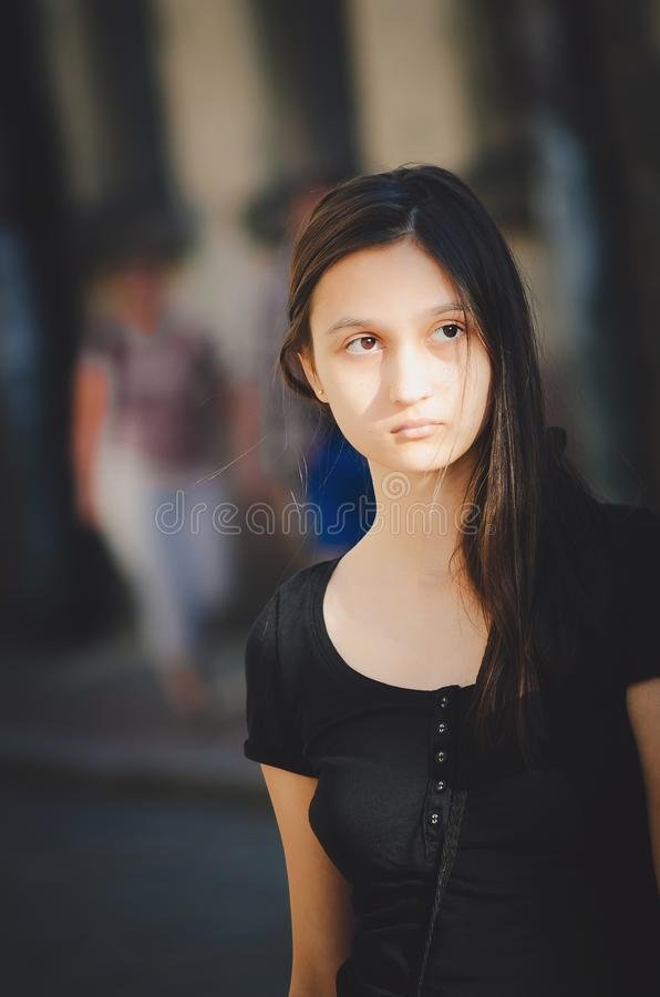 Belle jeune fille avec de longs cheveux foncés à la lumière du soleil photo stock