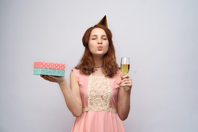 Belle jeune fille avec de longs cheveux rouges tenant un verre de cadeau de champagne et de boîte photographie stock libre de droits
