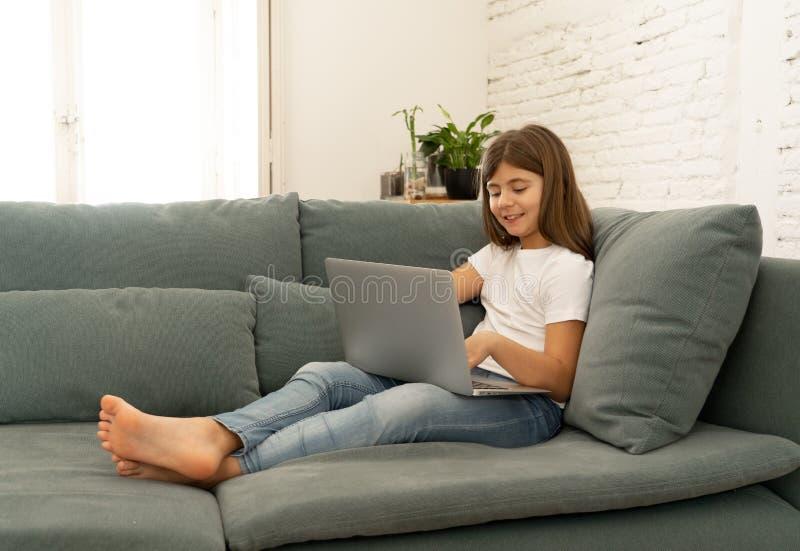 Belle jeune fille avec du charme mignonne jouant et surfant l'Internet sur l'ordinateur portable ? la maison photographie stock libre de droits