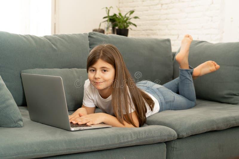 Belle jeune fille avec du charme mignonne jouant et surfant l'Internet sur l'ordinateur portable ? la maison image stock
