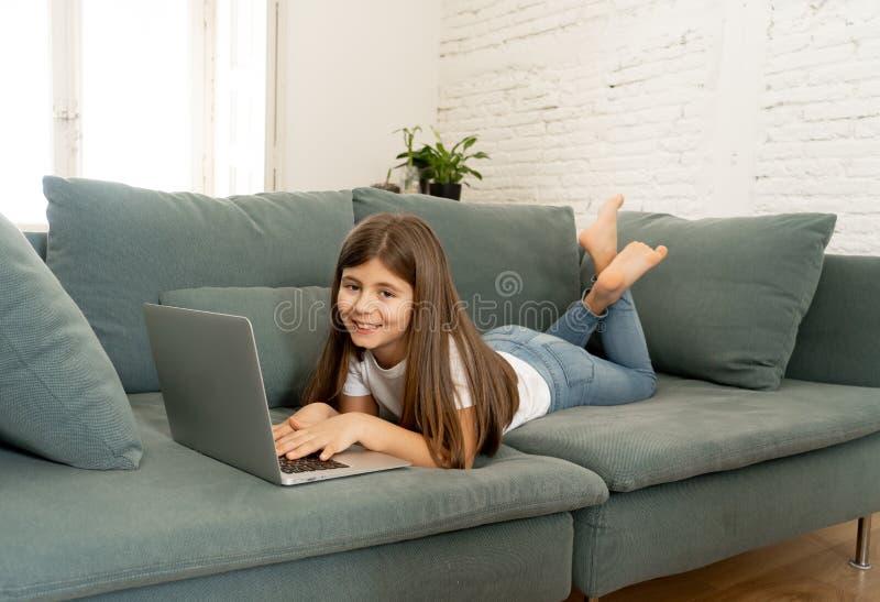 Belle jeune fille avec du charme mignonne jouant et surfant l'Internet sur l'ordinateur portable ? la maison photo libre de droits