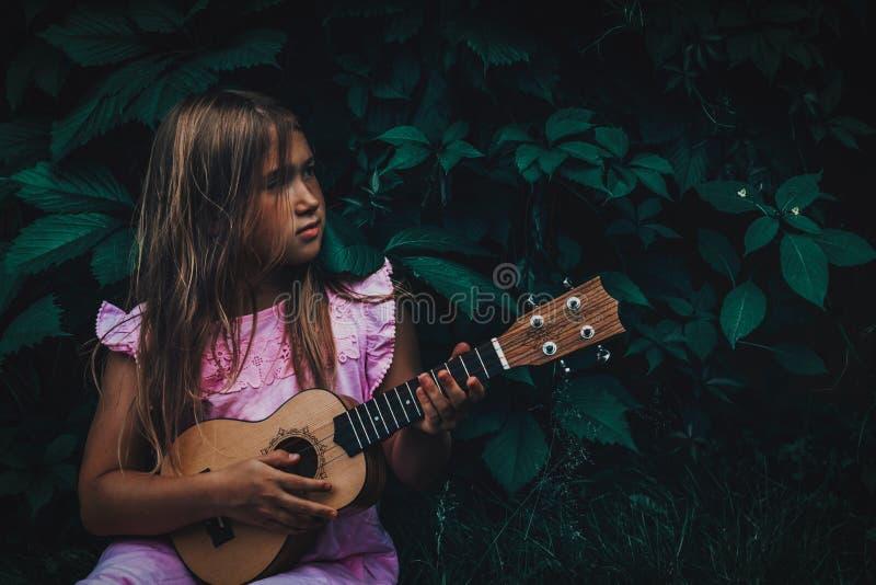 Belle jeune fille avec l'ukulélé image libre de droits