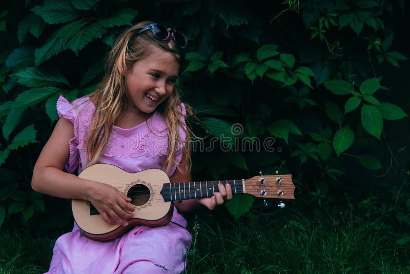 Belle jeune fille avec l'ukulélé photographie stock