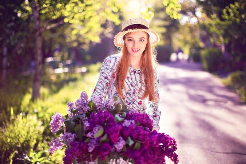 Belle jeune fille avec la bicyclette et les fleurs de vintage sur le fond de ville à la lumière du soleil extérieure photo stock