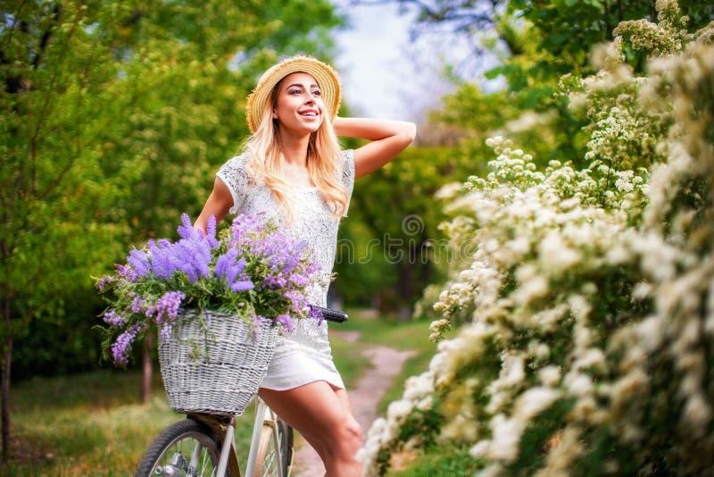 Belle jeune fille avec la bicyclette et les fleurs de vintage sur le fond de ville à la lumière du soleil extérieure image stock