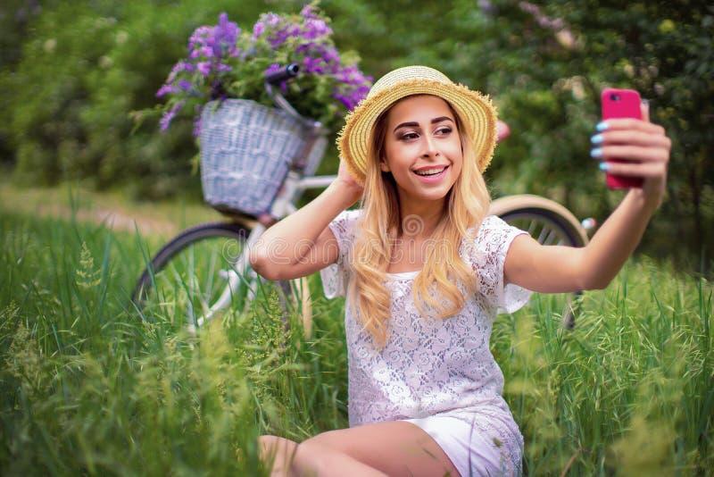 Belle jeune fille avec la bicyclette et les fleurs de vintage sur le fond de ville à la lumière du soleil extérieure photographie stock libre de droits