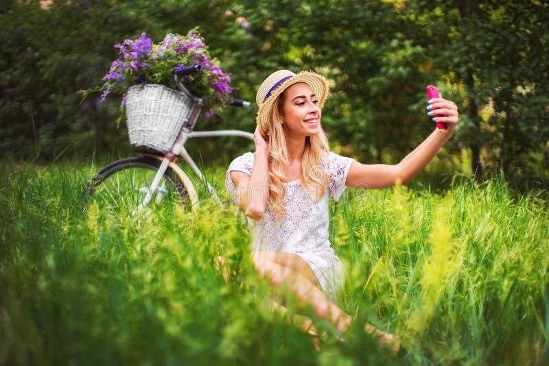 Belle jeune fille avec la bicyclette et les fleurs de vintage sur le fond de ville à la lumière du soleil extérieure photographie stock
