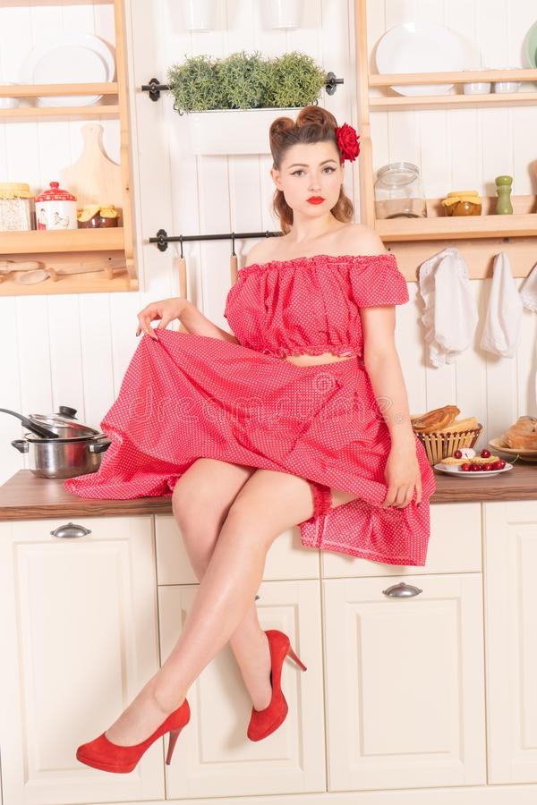Belle jeune fille avec la fleur dans ses cheveux posant dans la goupille rouge vers le haut de la robe de point de polka à la mai photo libre de droits