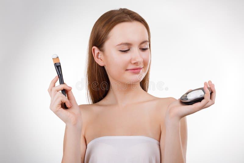 Belle jeune fille avec la grande brosse blanche Nettoyez les produits de visage Verticale de beauté photographie stock libre de droits