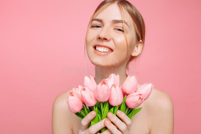 Belle jeune fille avec la peau propre tenant un bouquet des tulipes roses, sur un fond rose photos libres de droits