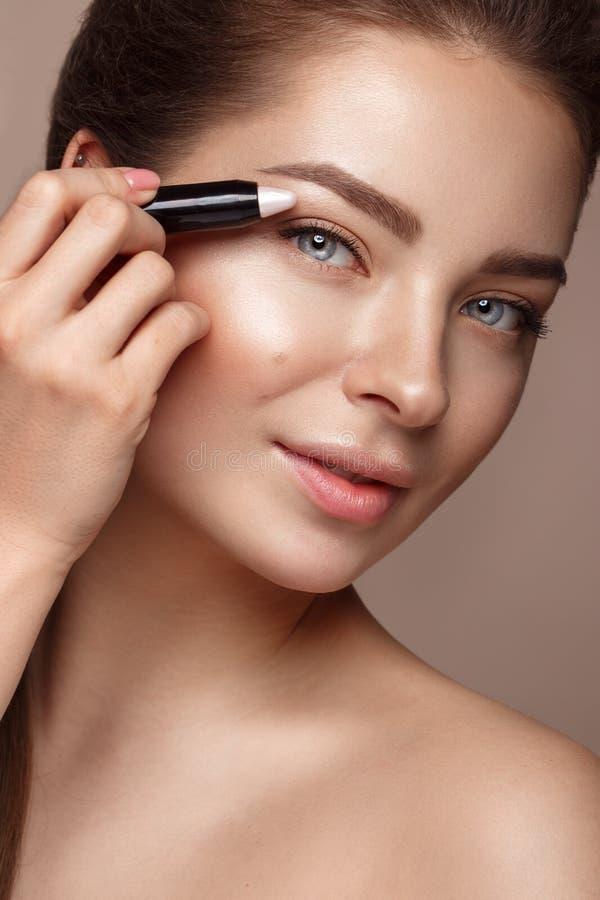Belle jeune fille avec le crayon nu naturel de maquillage et de barre de mise en valeur Visage de beauté images stock
