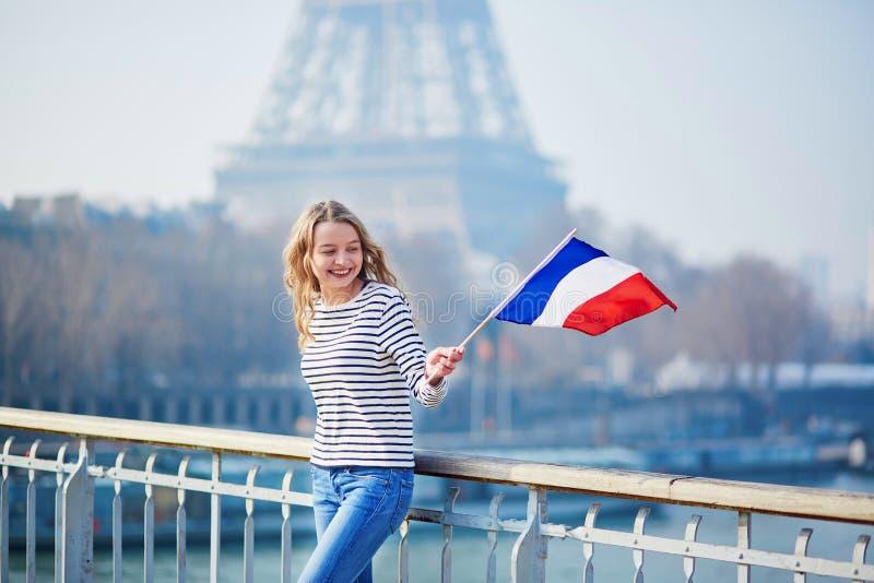 Belle jeune fille avec le drapeau national français près de Tour Eiffel photo stock