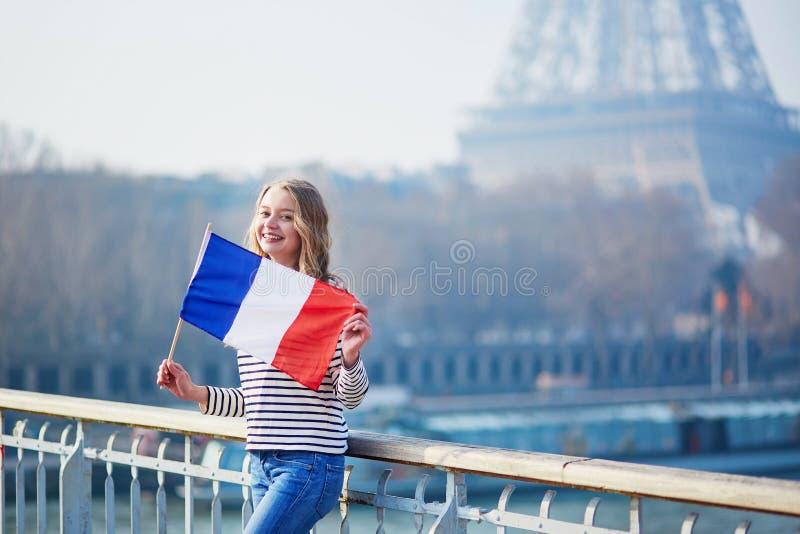 Belle jeune fille avec le drapeau national français près de Tour Eiffel images libres de droits