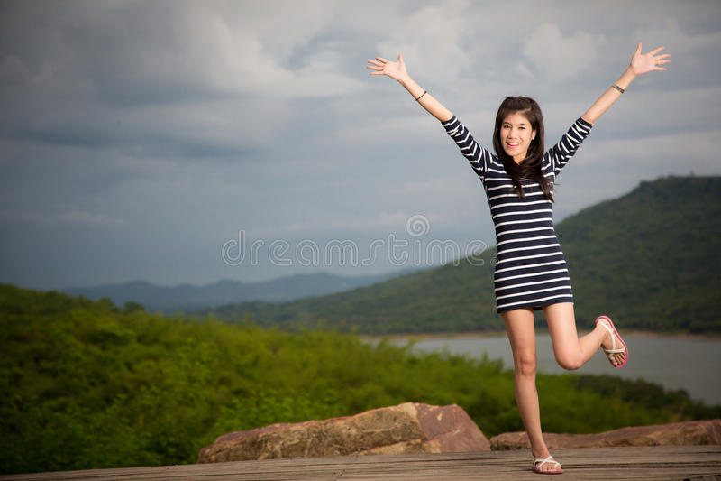 Belle jeune fille avec le fond de rivière et de ciel bleu photos stock