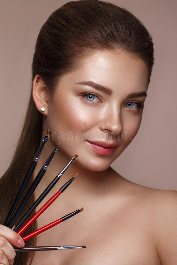 Belle jeune fille avec le maquillage nu naturel avec les outils cosmétiques dans des mains Visage de beauté image libre de droits