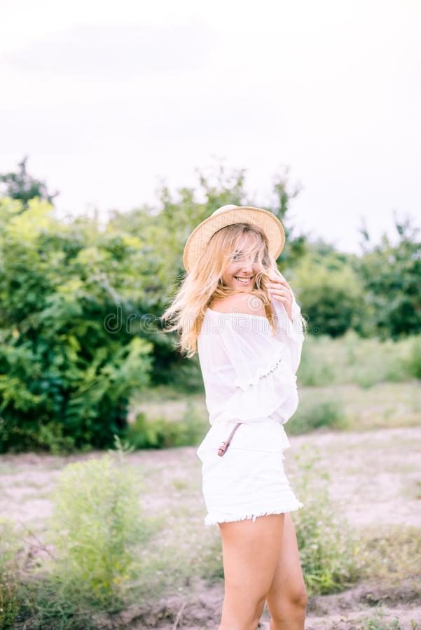 Belle jeune fille avec les cheveux blonds ayant l'amusement dans le jardin d'été photos libres de droits