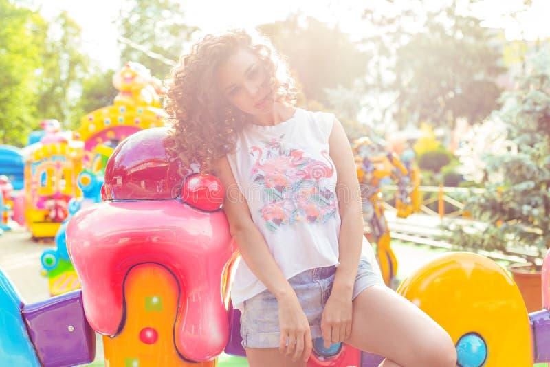 Belle jeune fille avec les cheveux bouclés dans des shorts de denim et le T-shirt blanc en parc d'attractions images stock