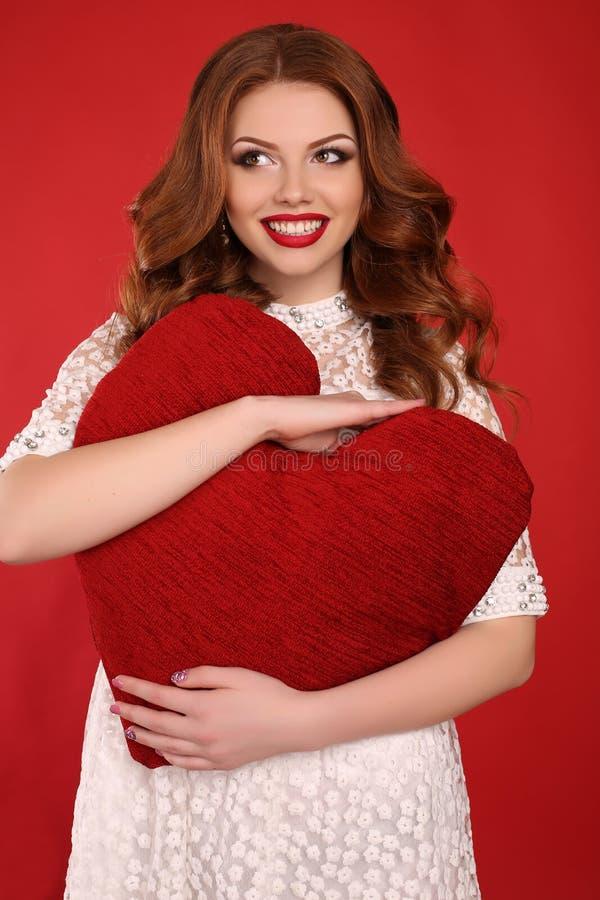Belle jeune fille avec les cheveux foncés et le maquillage lumineux, dans la robe élégante tenant le grand coeur rouge dans des m photographie stock