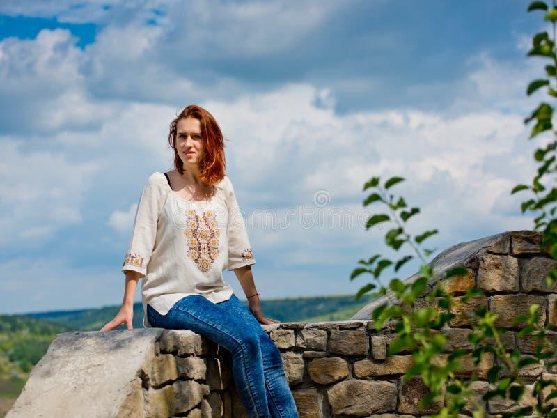 Belle jeune fille avec les cheveux rouges posant contre la nature images stock