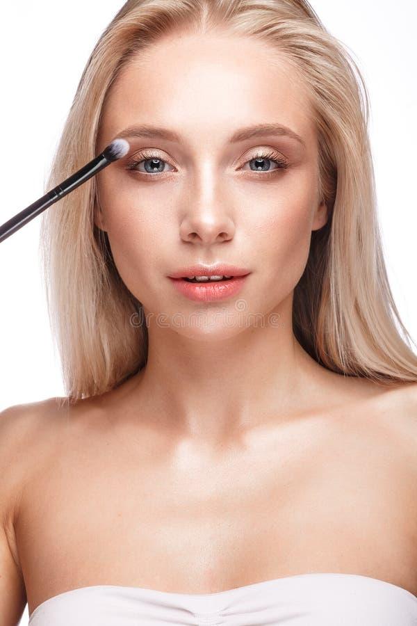 Belle jeune fille avec un maquillage naturel léger, une brosse de fard à paupières et une manucure nue Visage de beauté image libre de droits