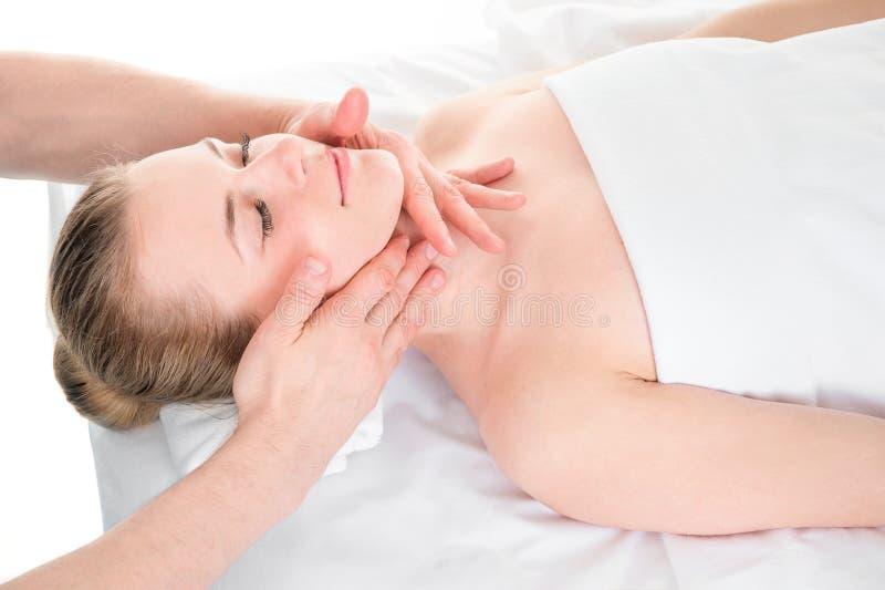 Belle jeune fille ayant le massage de visage dans le salon de station thermale images stock