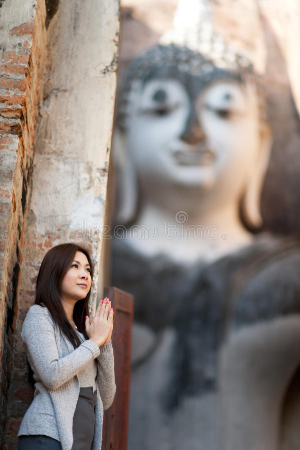 Belle jeune fille bénissant grand Bouddha photo stock