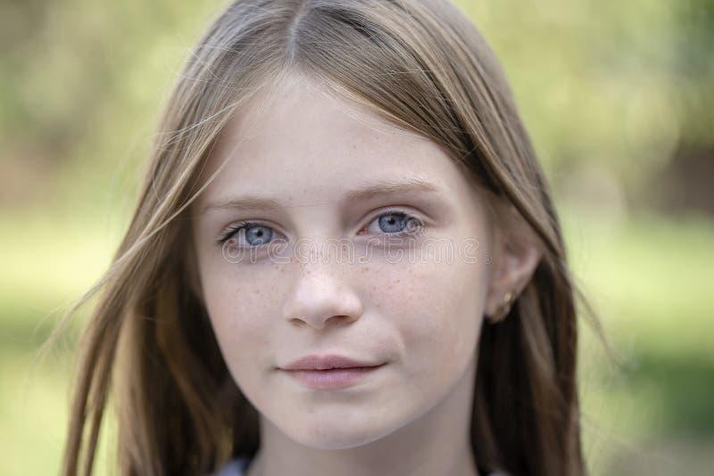 Belle jeune fille blonde avec des taches de rousseur dehors sur le fond de nature, portrait de plan rapproché photographie stock libre de droits