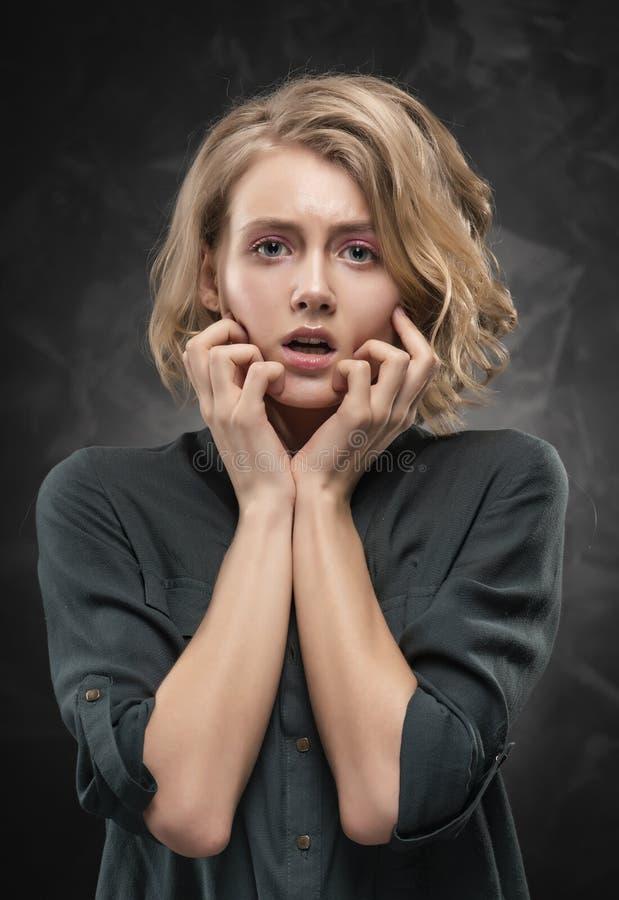 Belle jeune fille blonde avec la coiffure en d?sordre et le maquillage nu, utilisant une chemise et des jeans posant avec ?motion photographie stock