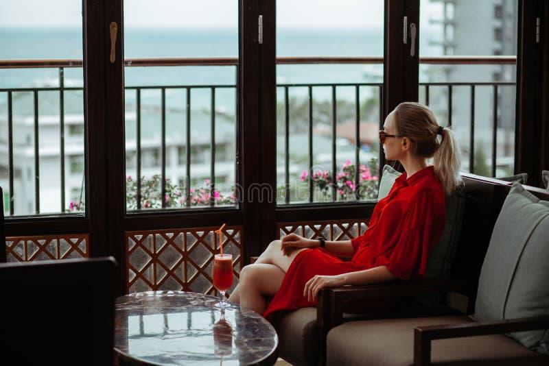 Belle jeune fille blonde dans la robe et des lunettes de soleil rouges buvant le cocktail rouge d'un verre sur une terrasse ouver image stock