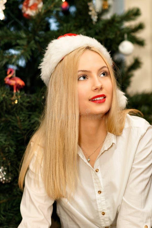 Belle jeune fille blonde dans le chapeau rouge de Santa à Noël photos libres de droits