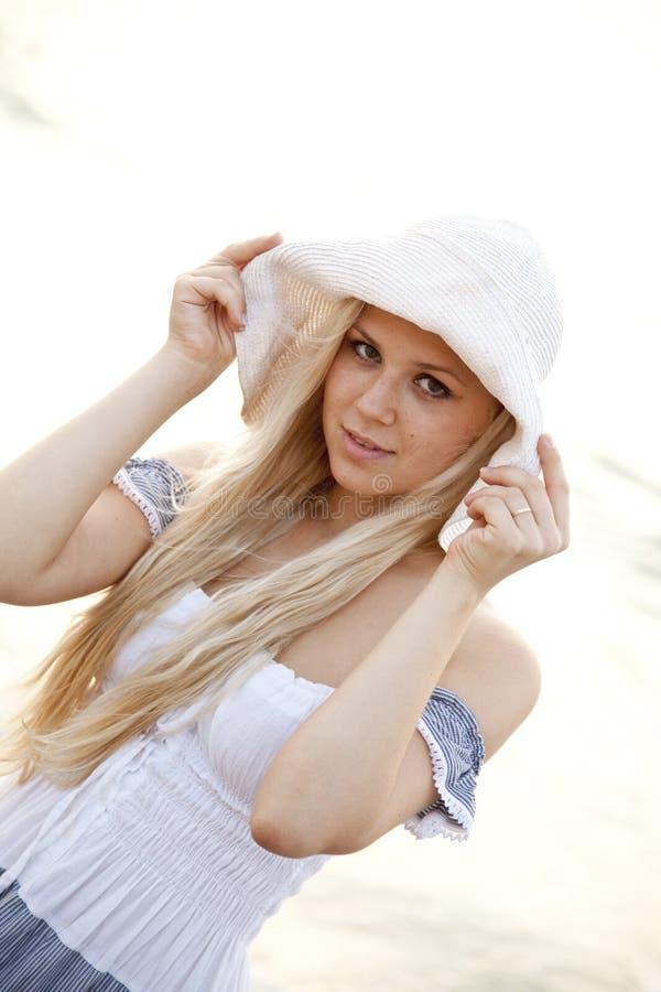 Belle jeune fille blonde dans le chapeau sur la plage image libre de droits