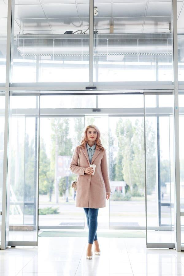 Belle jeune fille blonde dans un beau manteau beige, des jeans et des talons hauts photos libres de droits