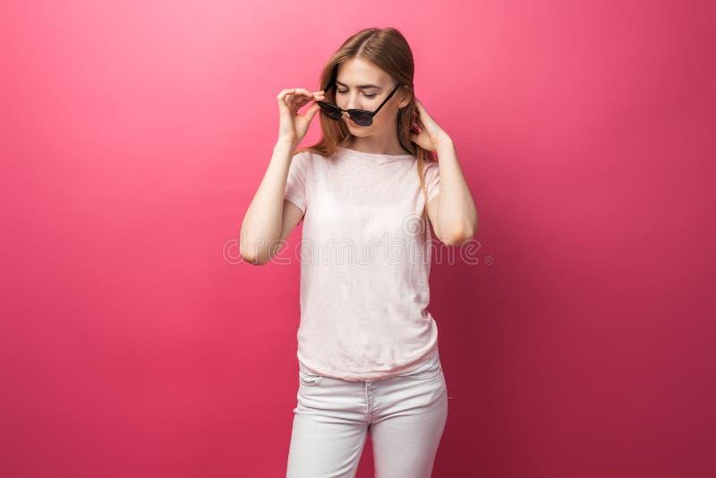 Belle jeune fille blonde en verres se tenant sur les jeans de port de fond rose, sourire blanc de sourire de neige de dessus rose image stock