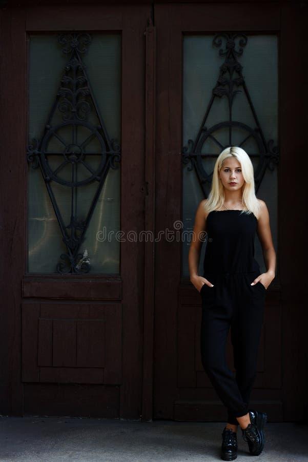 Belle jeune fille blonde posant sur le fond des portes de Bourgogne Femme sexy dans une robe noire La fille sur le fond image libre de droits