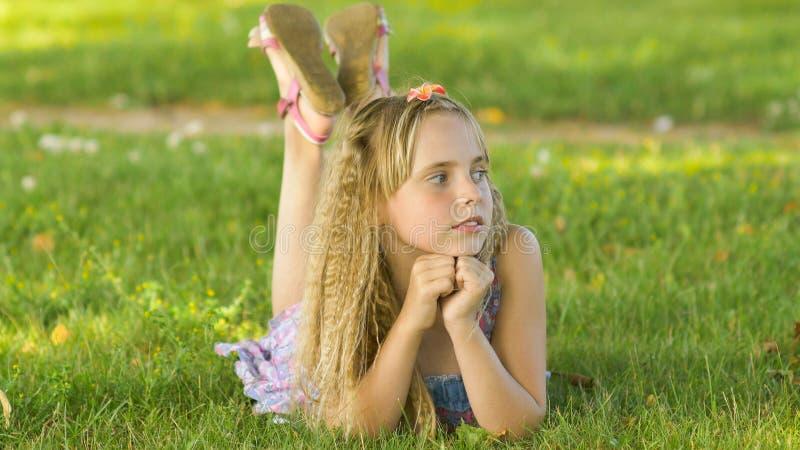Belle jeune fille blonde se trouvant sur un champ, herbe verte Appréciez dehors la nature Fille de sourire en bonne santé se situ photo libre de droits