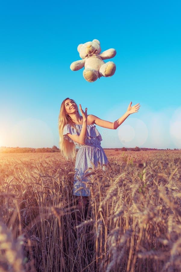 Belle jeune fille bronzée pendant l'été dans une robe légère, un jour ensoleillé lumineux Jetez un jouet d'ours de nounours dans  photo stock