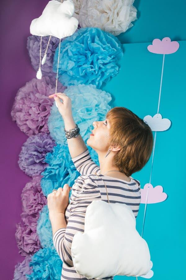 Belle belle jeune fille caucasienne tenant les nuages mous blancs sur le fond bleu image stock